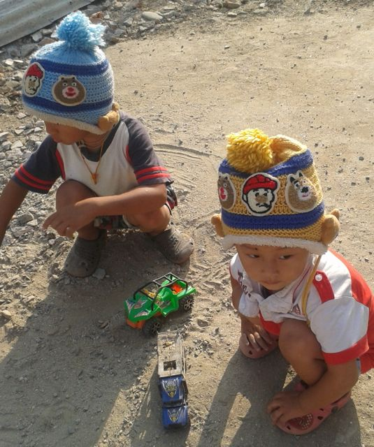 Jasper and Komol playing with trucks together