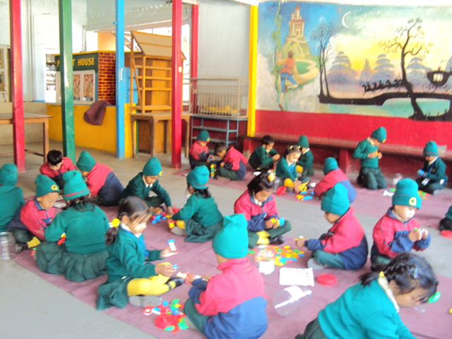 Kindergarten students, in their school uniforms, seated on the floor playing