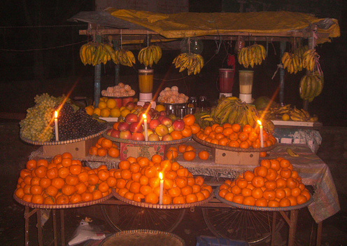 A market cart of oranges and bananas lit by candlelight