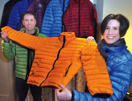 Liz and Len holding bright jacket in front of an array of colourful jackets
