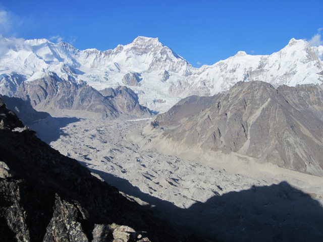Enormous glacier covered in rock debris filling a valley below Cho Oyu
