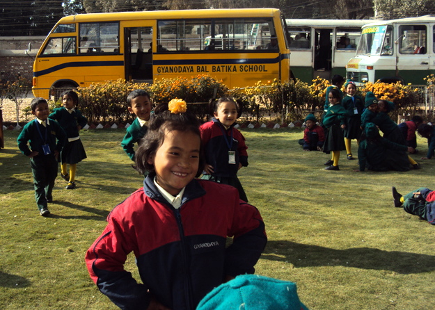 Resmi dancing toward the camera in front of the school bus