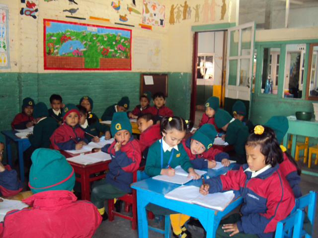 Resmi and other kindergarten children seated at tables, writing