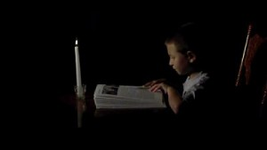 Boy reading in near-total darkness by candlelight
