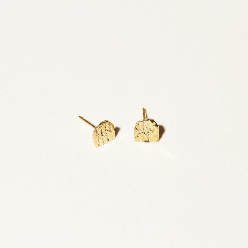 The Arc Stud Earrings are mini studs that are textured and measure an 1/8 inch. Elongated half-circles.