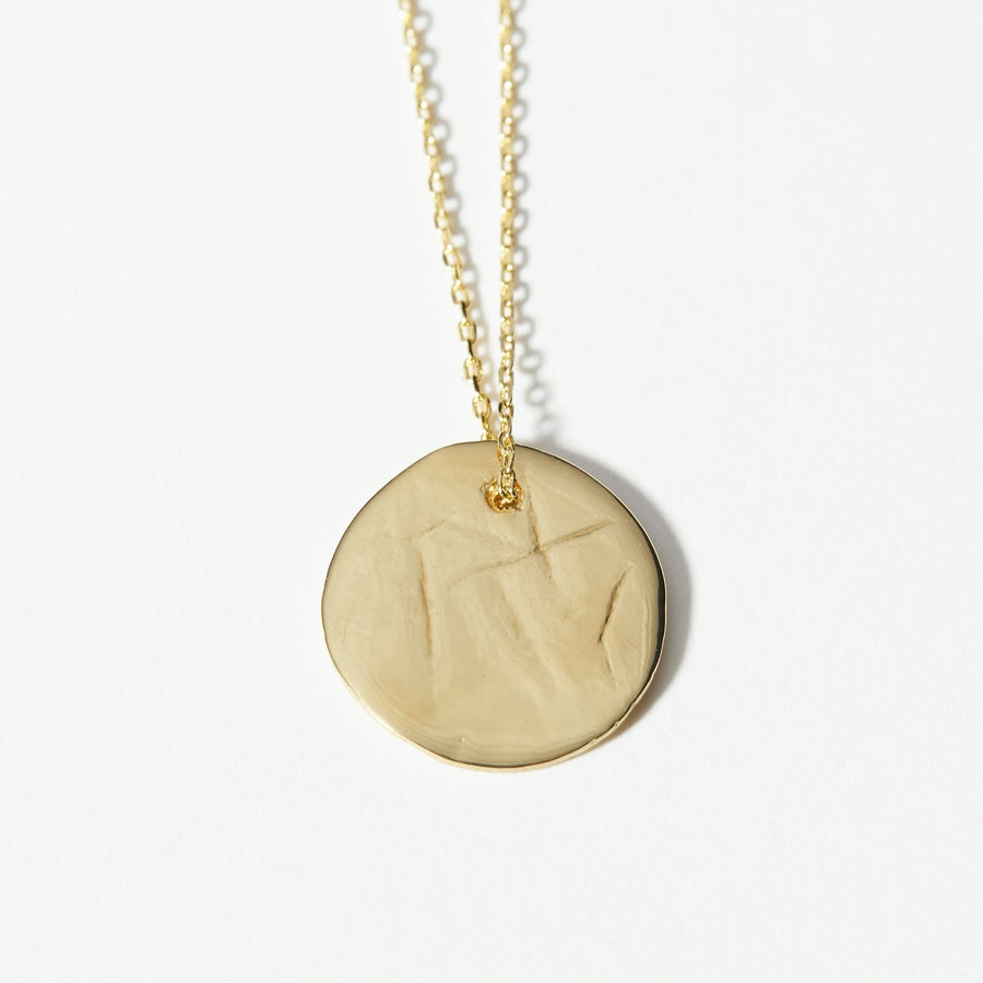 The Lunar pendant was handmade in clay and cast in 14k gold plate. Slightly textured surface and bright finish.