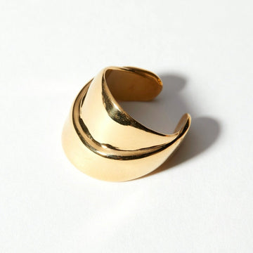 Overlapping wide bands of metal were inspired by the landscape. The Strata Ring in solid brass.
