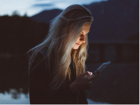 Woman Looking At Phone Receiving Blue Light Damage