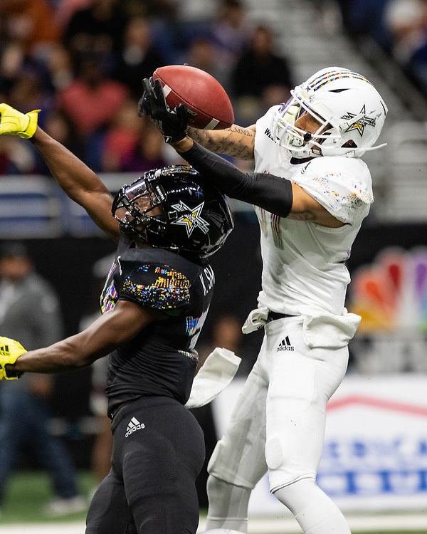 A football wide receiver jumps to catch a pass in the 2018 All-America Bowl.