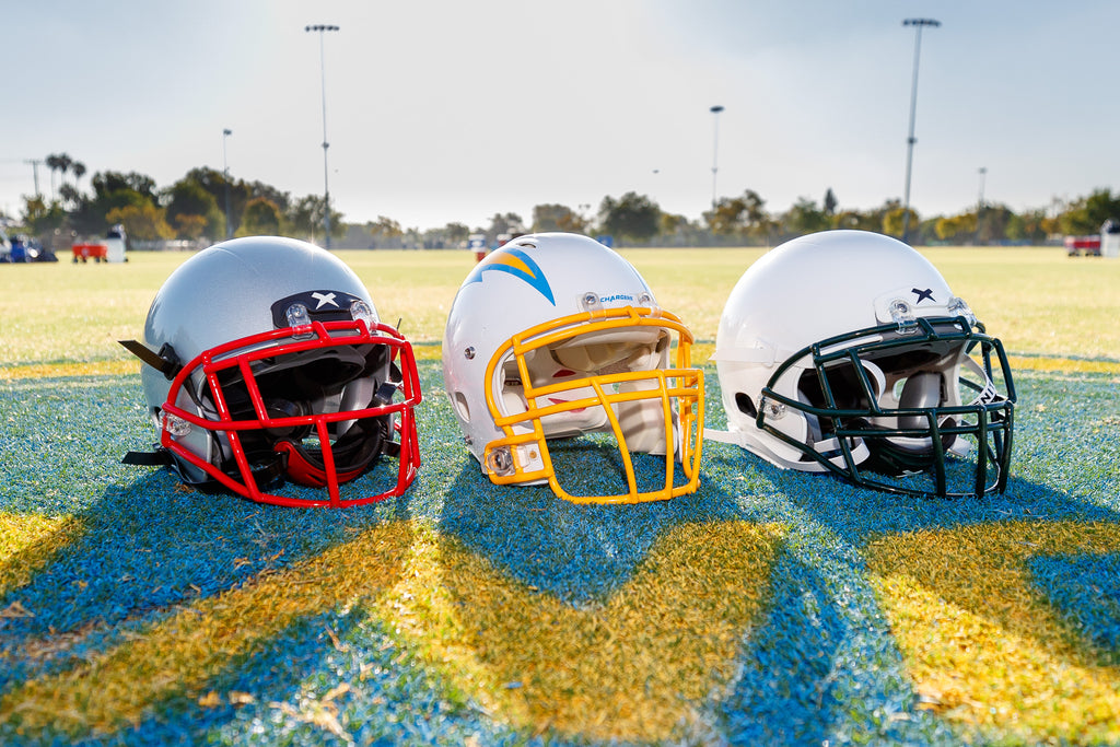 Two Xenith X2E+ Varsity football helmets sit on each side of a Los Angeles Chargers helmet on display at the Chargers practice field.