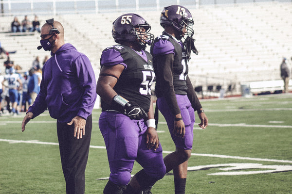 Everman Bulldogs Coach with Two Players on Football Field