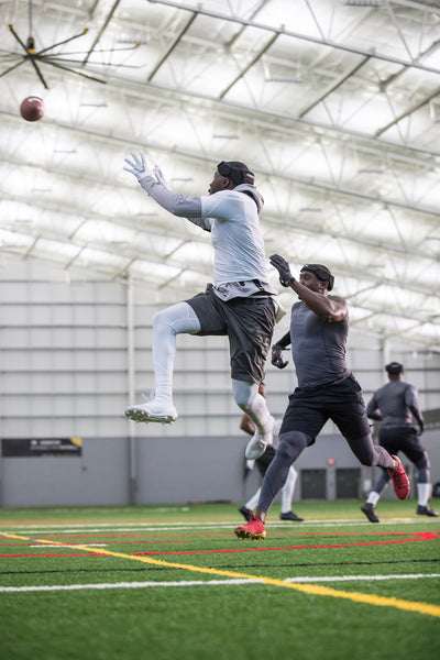 Two players jump to reach a football in a 7 on 7 game.