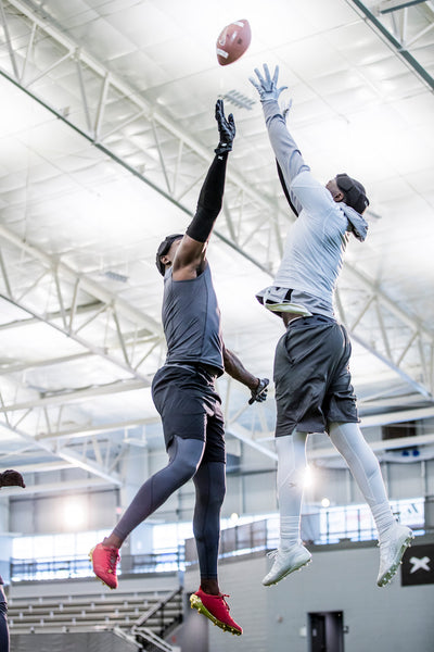 Two 7-v-7 football players jump to reach for a football