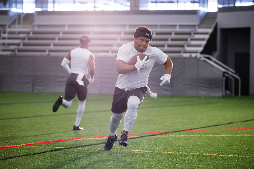 Football players running a route in a 7v7 non-tackle football game wearing the Xenith LOOP.