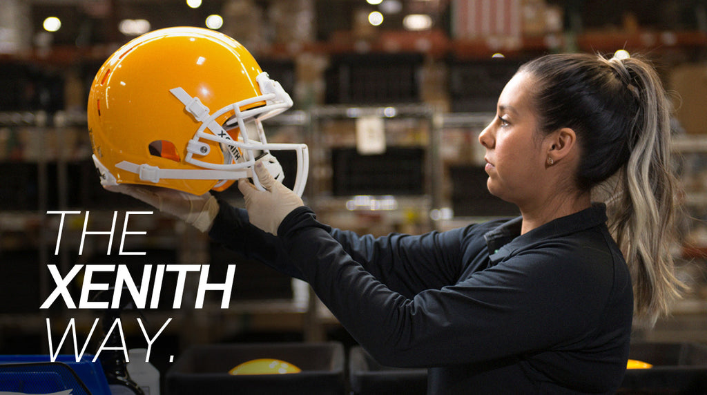 Xenith employee inspecting X2E+ helmet after reconditioning process