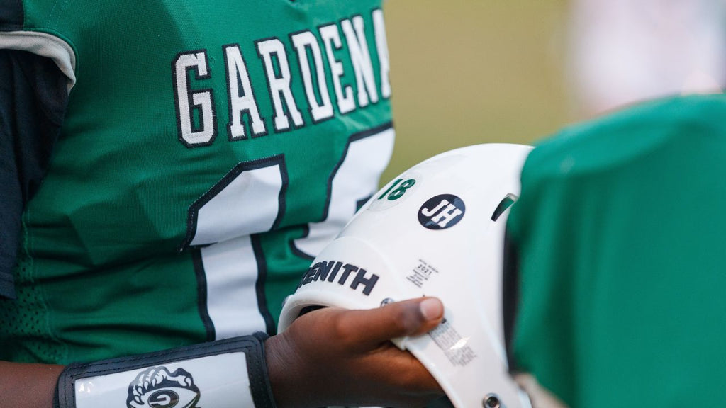 Gardena High School football player holds his Xenith helmet, featuring a personalized sticker for his fallen teammate.