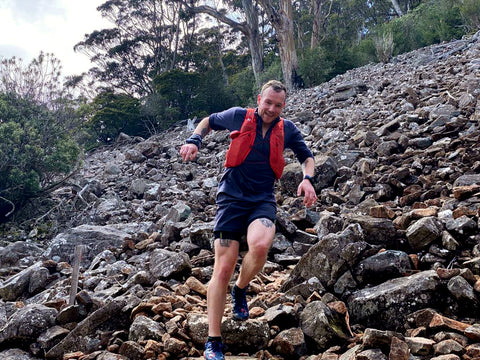 A man wear grey shorts and shirt, with a red trail running vest pack on, running haphazardly down a steep hill seemingly made up entirely of rocks