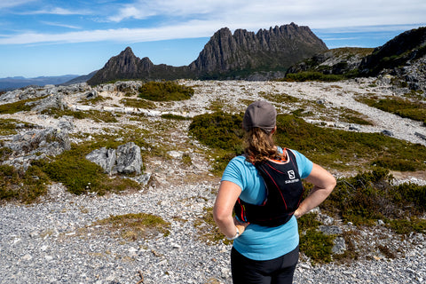 A female trail runner looks out across a chasm to view Cradle Mountain opposite her. It is a clear day with just a few white clouds behind the mountains peaks.