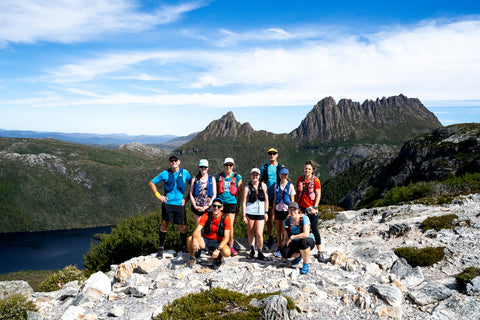 A group of very happy looking trail runners pose smiling at the camera in front of cradle mountain