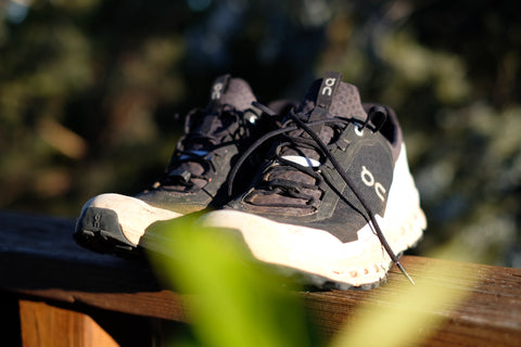 OnCloud Ultra trail running shoes sitting in a patch of sun, the toe of one shoe is partially covered by an out of focus bright green leaf