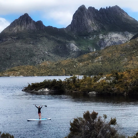 woman on paddle board poses on dove lake infant of Cradle Mountain