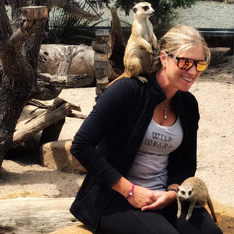 woman with meerkat sitting on her
