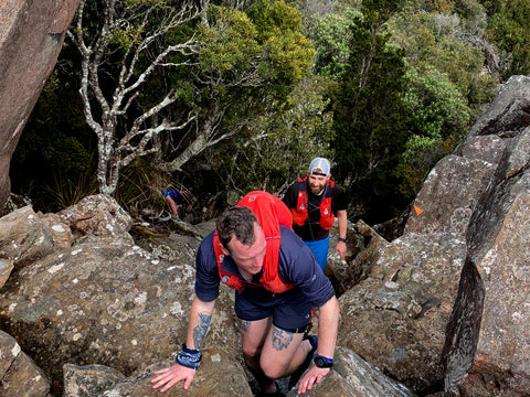 a man in a grey icebreaker merino running top and red Salomon vest pack climbing up bolders, a man behind him laughs