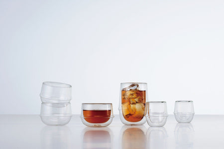 vier leere und kleine transparente Glas Teetassen neben zwei transparenten Glas Teetassen mit flüssigem Tee in ihnen auf weissem Hintergrund - four empty and small transparent glass tea cups next to two transparent glass tea cups with liquid tea in them on white background