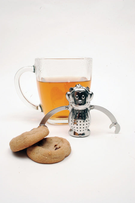 Tee-Aufgusskorb Teegeschirr in Affenform neben einer Tasse Tee - Monkey Tea Infuser Teaware Kikkerland next to cup of tea