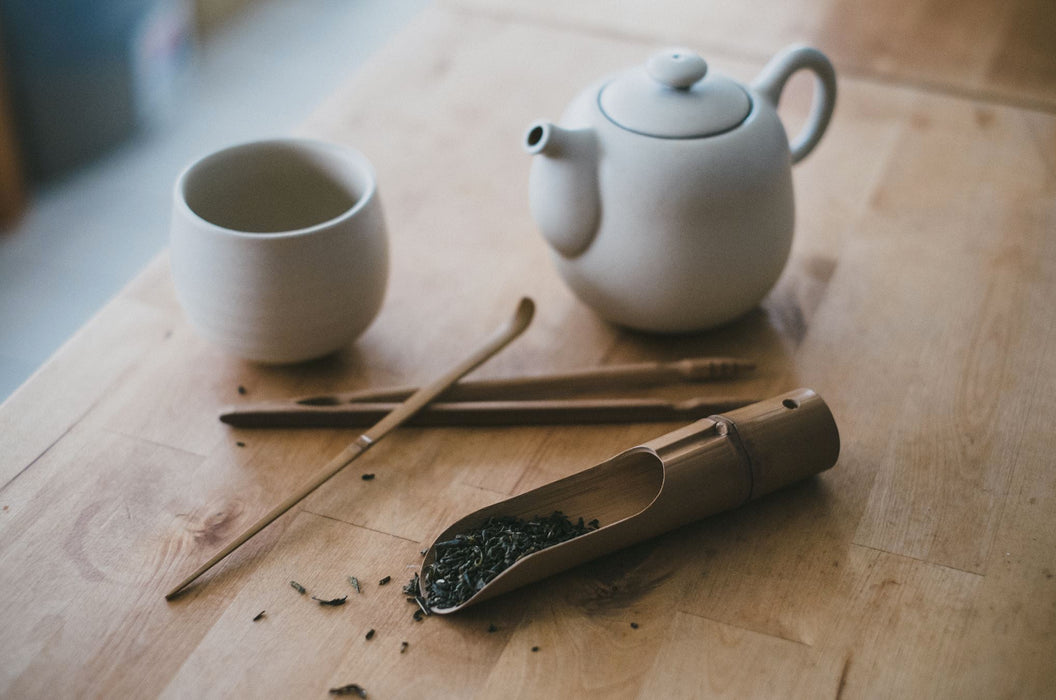 Oolong Loser blatt Tee im Holzklammer neben Teetasse aus weisser Keramik und Teekanne aus weisser Keramik auf Holztisch - Loose-leaf Oolong tea in wooden clip next to a white ceramic teapot and white ceramic teacup on wooden table