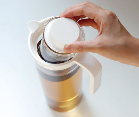 Hand stellt Eistee-Ei in hohe transparente Teekanne  - hand puts iced tea infuser in tall transparent tea jug