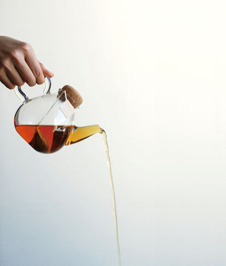 Hand giesst braunen flüssigen Tee aus transparenter Teekanne - hand pours brown liquid tea from transparent teapot