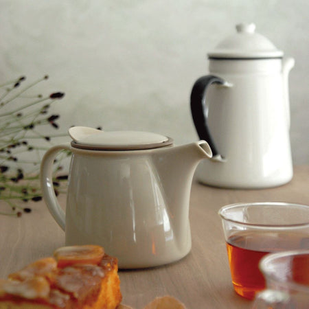 BRIM graue Edelstahl Teekanne neben transparenten Tee Kasse - Stainless Steel BRIM teapot next to transparent teacups on a wood table Teaware Kinto