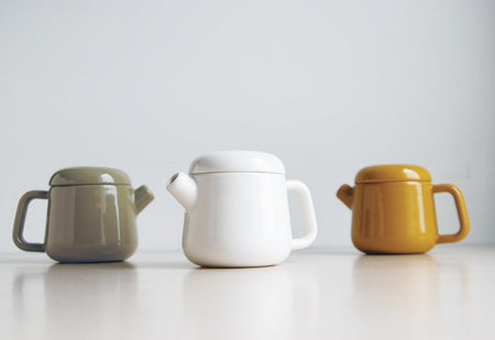 Grune TRAPE Porzellan Teekane neben Weisse TRAPE porzellan Teekane neben Gelbe TRAPE porzellan Teekane auf grauen Hintegrund - green teapot next to white porcelain teapot next to yellow porcelain teapot on grey background Teaware Kinto