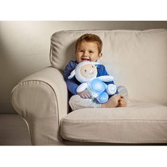 Chicco First Dreams Lullaby Sheep Night Light (Blue) - lifestyle image, shown here used as a cuddly toy by a toddler