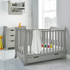 Obaby Stamford Mini Sleigh Cot Bed (Warm Grey) - lifestyle image, shown here with the changing unit and the shelf (shelf available separately)