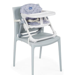 Chicco Chairy Booster Seat (Bunny Grey) - quarter view, showing Chairy fixed onto a dining chair (chair not included)