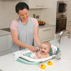 ClevaMama ClevaBath - The Bath Sink (Aqua) - lifestyle image, shown here with baby in a kitchen sink