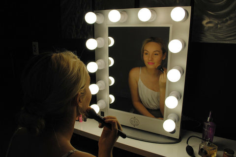 Woman Doing Makeup in Mirror with LED Lights