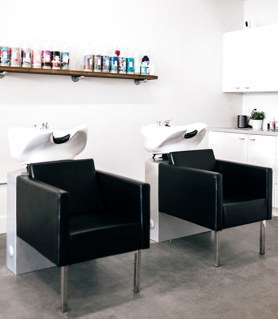 salon shampoo station with simple chairs and floating shelves