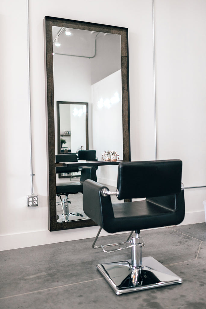 simple chair and large mirror in a salon