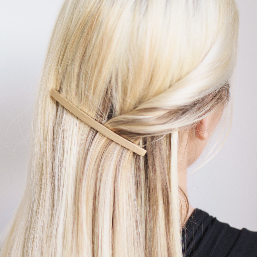 close up of blonde hair styled with a simple gold hair accessory