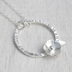 Silver flower on hammered circle necklace