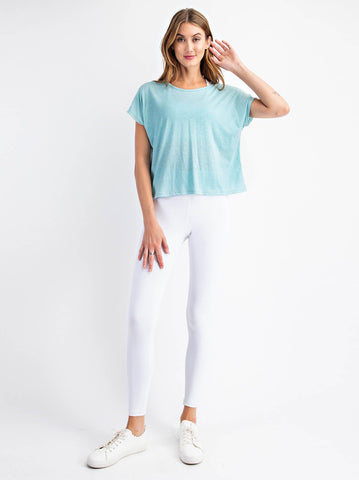 woman standing with a teal top and white leggings