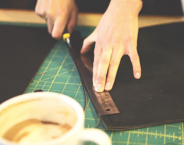Market Canvas Leather designer handcutting leather piece with exacto knife - latte in the foreground