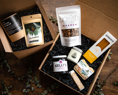 Two cardboard boxes filled with tumbler case, hot toddy kit, bag of granola, jar of jam, small bar of chocolate, candle in a glass jar, bar of beer soap, package of honey sticks. They're all sitting on black crinkle paper that are in boxes. Boxes are on wooden table with green eucalyptus around the boxes.