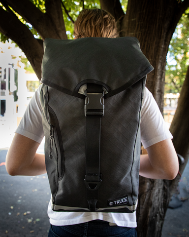 Man in white tee wearing a grey backpack