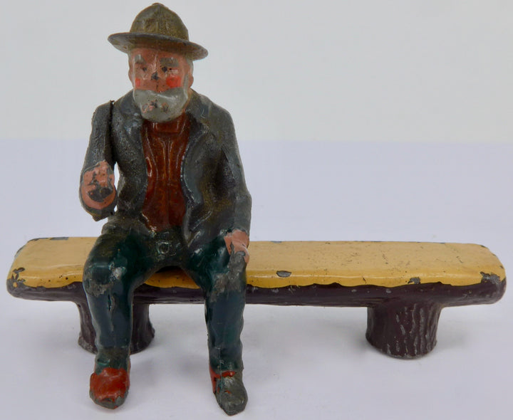 Britains aged villager on log seat, grey