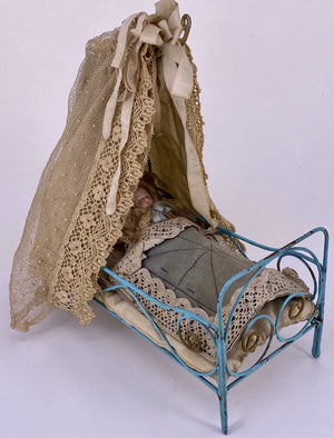 wire doll bed with original bed clothes and doll