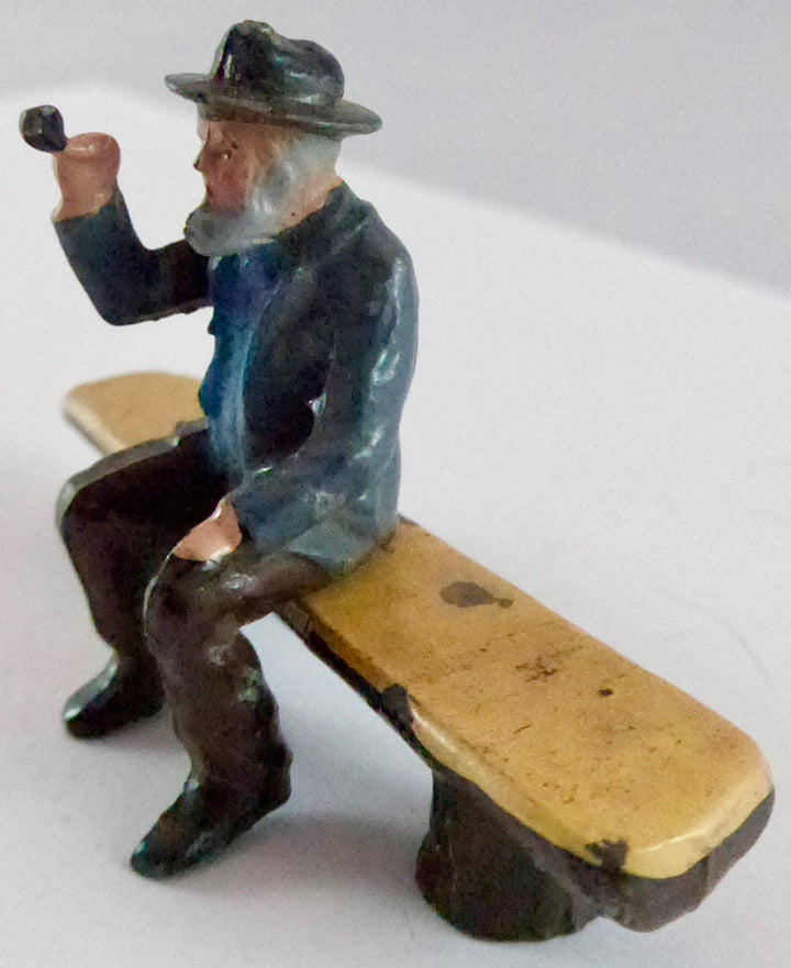 Britains aged villager with pipe on log seat, grey